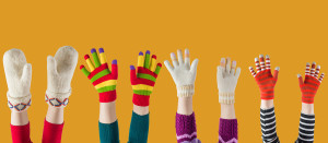 winter mittens and gloves on orange background